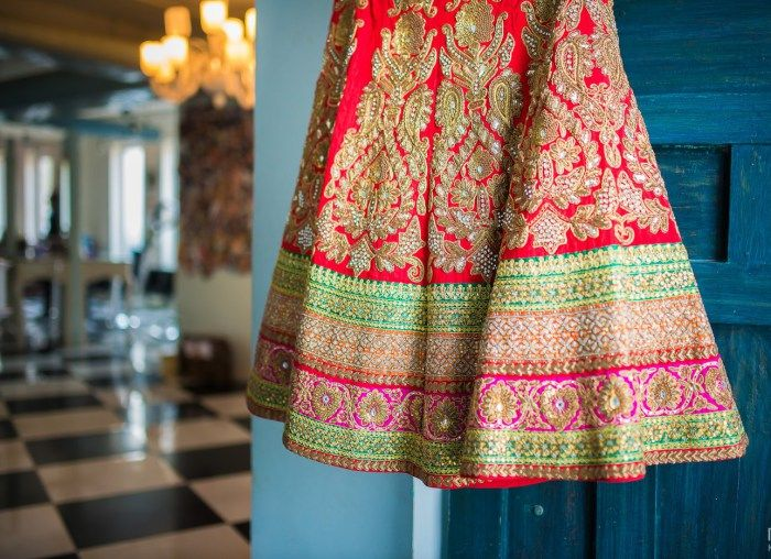 Bridal lehenga with a saturated chilli red raw silk base, has a vibrant green along with a small flash of pink in the borders