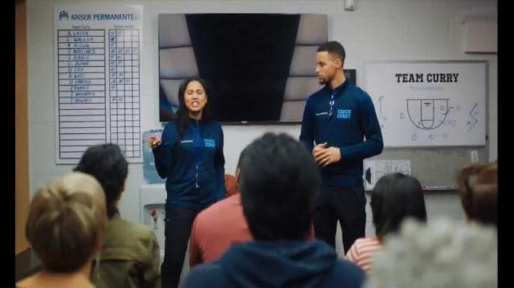 """Ayesha and Stephen Curry are holding a """"Bad Habit Review"""" session with a small group. On the screen, they review some refrigerator footage of one guy eating late-night snacks including pizza topped with whipped cream and a fist full of spaghetti. The audience watches with disgust and horror, and Stephen dismisses the man on some sort of foul called a """"Flavor 2."""" Ayesha puts Stephen on the receiving side of humiliation when she shows his bad habit video of chewing on his mouthguard. Kaiser…"""