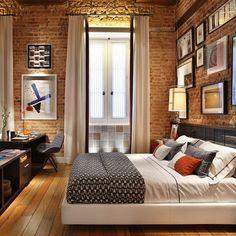 Parede tijolo rústico, pé direito duplo, cortinas altas, quadros, cama borda estofada, piso madeira