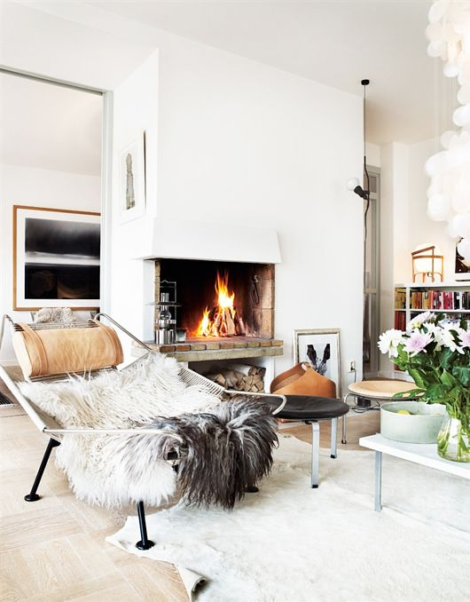 Scandinavian style is an comfy mix of modern straight lines, lots of white, woods and natural elements and always a fur throw or cowhide carpet