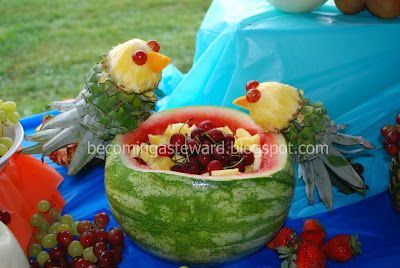 Pineapple parrots resting on a watermelon bowl, filled with fresh pineapple and cherries.
