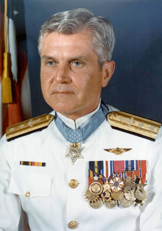 "Vice Adm. James Stockdale was leading his carrier group back to the USS Oriskany after a bombing run over North Vietnam. He was downed by anti-aircraft fire, broke his back and dislocated his knee, and was sent to the infamous prison camp known as the ""Hanoi Hilton."" There, as the senior officer he took over efforts to build morale and resist Vietnam efforts to create propaganda."