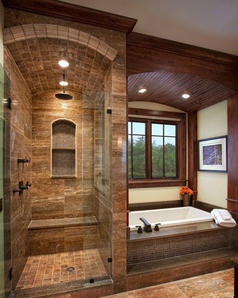 Love the tile and stone used in this shower. The arch detail, niches, and frameless glass inclosure would make a big impact in a small bathroom.