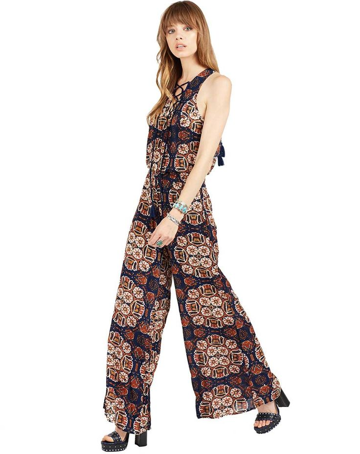 - Rayon sleeveless jumpsuit in our signature High Noon print - Lace up front neck - Tassel drawstring closure in back of neck - Plunging back - Wide leg pants - Model is wearing size Small - Measureme
