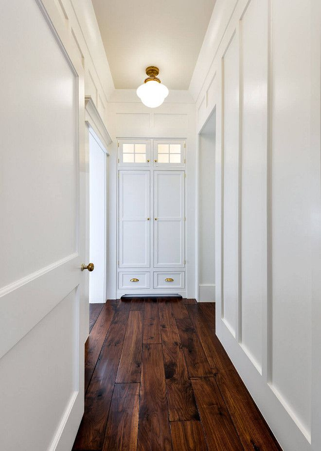hall with board and batten walls solid walnut hardwood floors and shaker linen closet