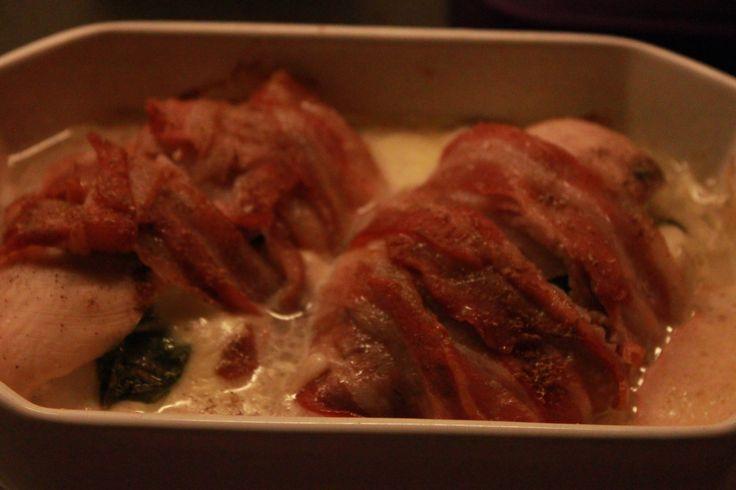 Ingredienser (2 personer): 2 kyllingefilet 1 stk frisk mozzarella ost 4 skiver bacon 6 blade frisk basilikum Salt og peber. Bønnechips til servering. Fremgangsmåde: Skær kyllingefileterne halvt ove...