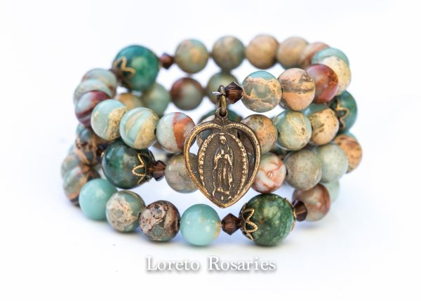 This is a full 5 decade rosary made with 8mm African Opal Jasper gemstones, 10mm African Jade Pater beads, solid bronze crucifix and Our Lady of Guadalupe medal on a stainless steel memory wire. $50.00