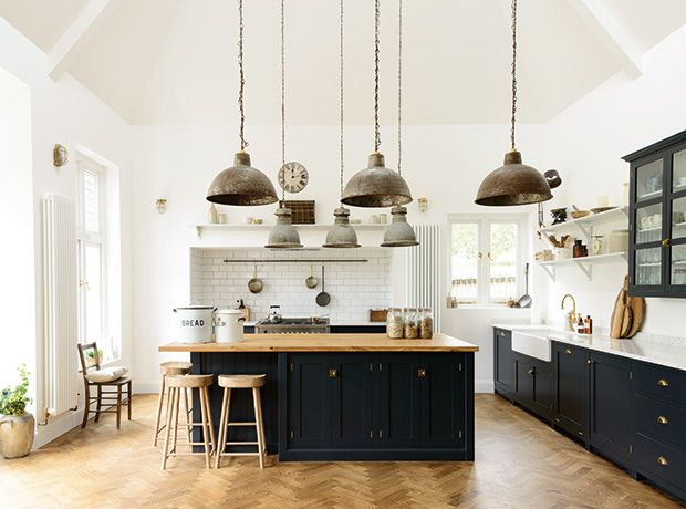 From the blonde wood herringbone floors to the dark-painted cabinets, everything about it is a master class in building character and charm. | Photographer: Courtesy of deVol Kitchens