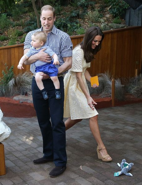 Catherine, Duchess of Cambridge picks up a toy bilby Prince George of Cambridge threw on the ground as Prince William, Duke of Cambridge holds Prince George of Cambridge during a visit to the Bilby Enclosure at Taronga Zoo
