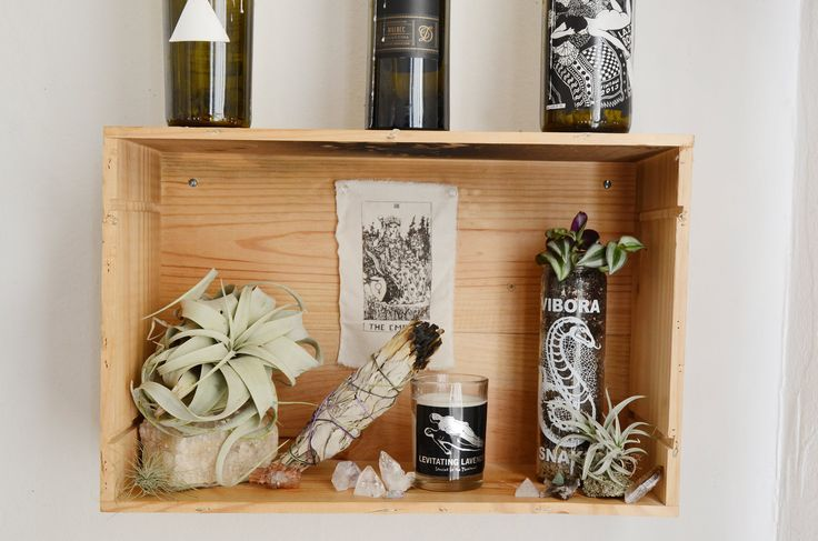 """Cheyenne's best friend, who happens to be a gallery curator, helped drill the wine box shrines straight into the wall. """"I fill the boxes with different objects and pictures I'm using to manifest and draw certain things into my life,"""" Cheyenne says."""