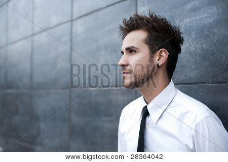 Hombre guapo joven mirando pensativo (piercing en la oreja)