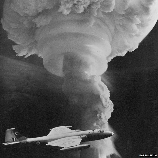 An RAF Canberra flying in front of a mushroom cloud caused by a hydrogen bomb detonation.