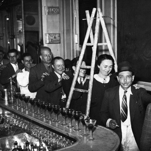 """Members of the """"Friday The Thirteenth Club"""" walk under a ladder in single file line at a meeting in a Paris bar. The club met every Friday 13th to do everything that superstitious people traditionally avoid (24 Vintage Pictures Of Paris Life In The 1920s"""