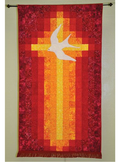 """Quilt a divine and stunning banner.   This beautiful, simple banner celebrates the Pentecost in a straightforward and bold way. The cross becomes a flame, and a dramatic use of color with batiks makes it really dynamic. This banner makes a great Easter or Christmas gift. Finished size is 39"""" x 69""""."""