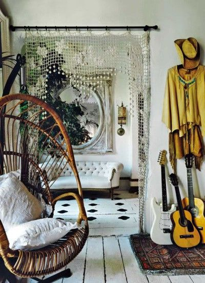 Boho living room featuring a wicker swing chair, beaded curtains and vintage inspired details.: