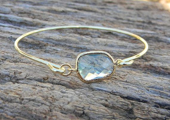 A gorgeous asymmetrical aquamarine glass charm (15 X 21 mm) adorns this trendy gold bangle bracelet. This bracelet makes the perfect gift (or to
