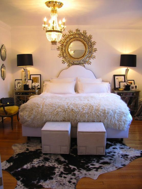 Suzie: Heights of Fashion - Amazing eclectic bedroom design with white camelback bed with nailhead trim, JCP canvas nailhead trim cube ottomans, cowhide rug, Borghese mirrored nightstands, mirrored horn lamps, venetian mirrors, crystal chandelier and sunburst mirror.