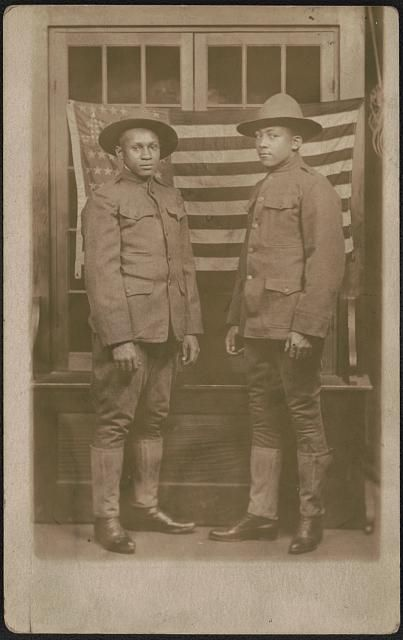 [Two unidentified African American soldiers in uniforms and campaign hats standing in front of American flag]