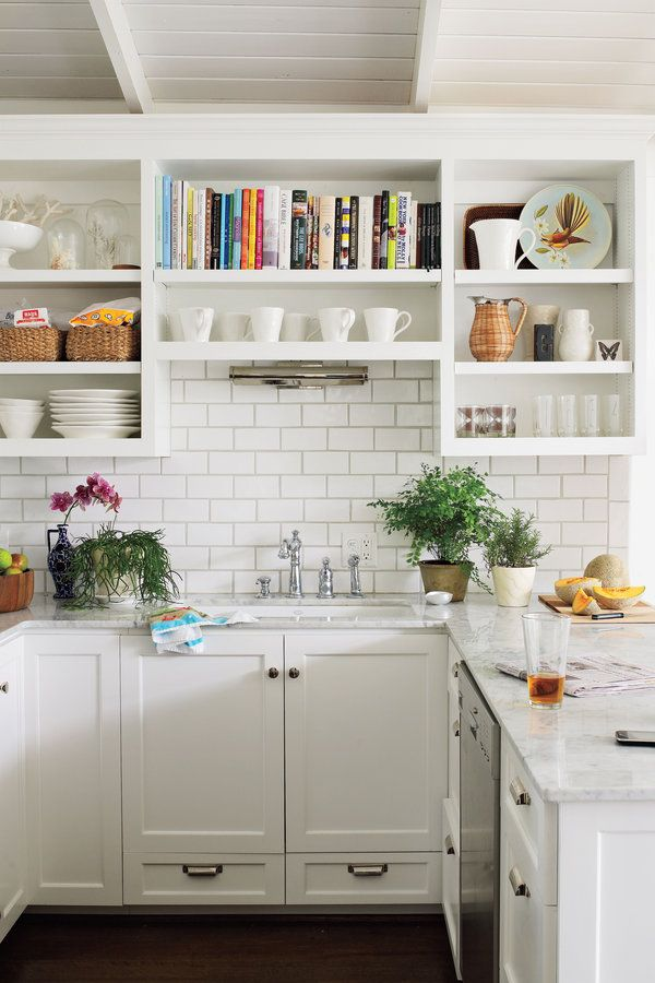 White makes this small kitchen feel open and spacious. The cabinets are painted the same crisp white (Pure White (SW7005) by Sherwin-Williams) that coats as the wall and vaulted ceiling. A ceramic subway-tile backsplash and sleek marble countertops complete the monochromatic look. Greenery adds a splash of color around the sink. Easy-to-access open shelving holds everyday basics, cookbooks, and decorative platters and pitchers