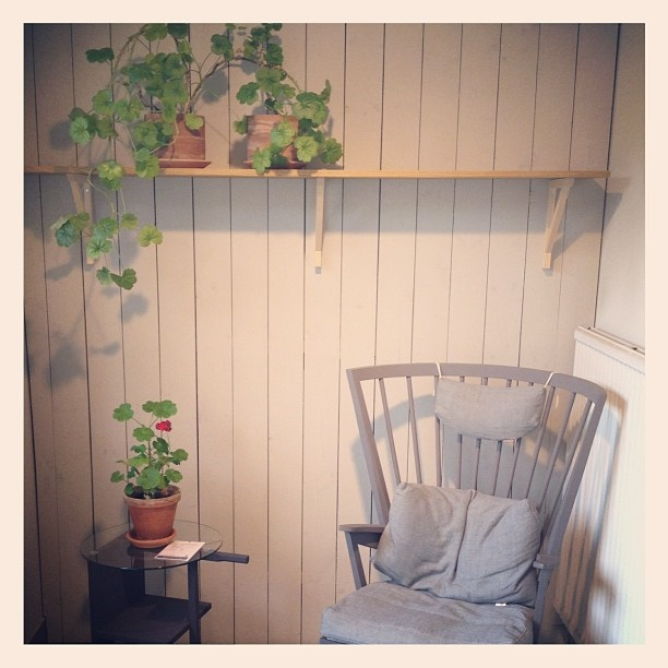 Norrgavel Länstol, grey wooden armchair, linen cushion, geranium on wall shelf
