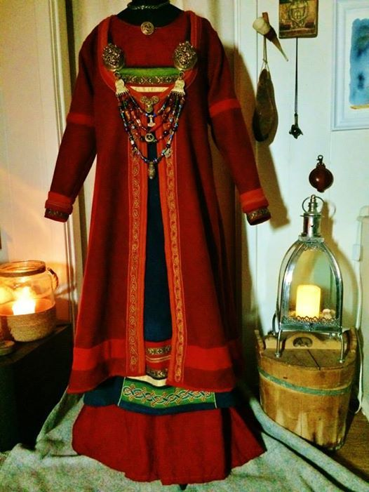 Beautiful viking ensemble - I love the bright colors! Hard to tell what style of apron dress is here, could be a fully sewn one or a wrap (they can look similar when draped on a mannequin) But they definitely have a front panel look going with having the trim just in the front on the bottom hem. I think the whole thing is lovely.