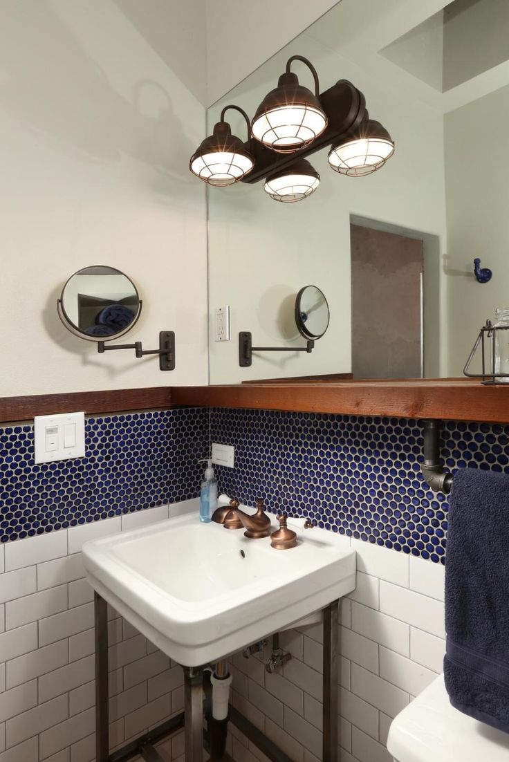 Reclaimed wood shelves add function to this custom bathroom renovation. In the space, contemporary blue penny tile mixes with traditional white subway tile for a layered, transitional feel. The space features antique bronze accents.