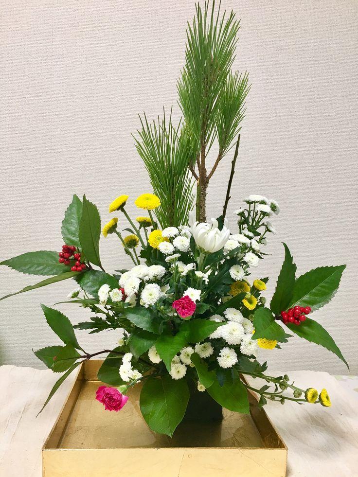 「迎春アレンジ」セールコーナのお花を使って自力で挑戦。松の葉をセンターにパラレルに立てて、左右に南天でライン構成。フォーカルは大きめの菊で。カーネーションをサブ構成に、マスの箱ウメとオアシス隠しをスプレー子菊で。