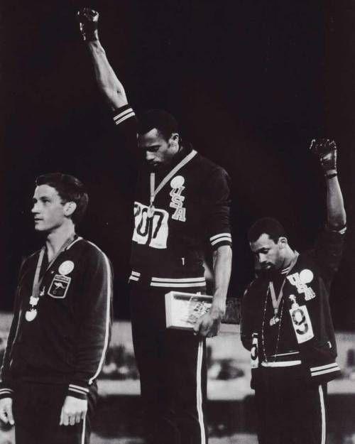 """fotografia bautizada como """"saludo Black Power de los Juegos Olímpicos de 1968"""" que fue una célebre señal de protesta de los derechos civiles negros en Estados Unidos. Tras finalizar la carrera de los 200 metros en los Juegos Olímpicos de México de 1968, los atletas afroamericanos Tommie Smith y John Carlos, medalla de oro y de bronce respectivamente, alzaron su puño envuelto en un guante negro mientras comenzaba a sonar el himno estadounidense. esto les basto ser expulsados de los juegos…"""