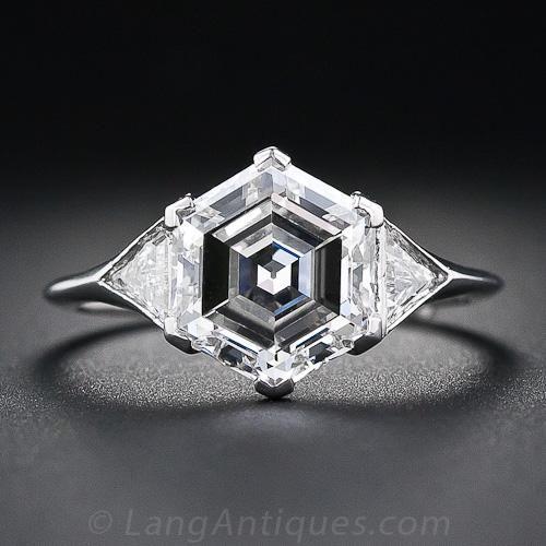 Un anillo de compromiso de diamantes de una belleza única Art Deco con un hexagonal diamante de corte fascinante y encantadora que pesa tan sólo nueve puntos tímidos de tres quilates. Esta roca rara y radiante se establece con púas chevron-forma entre un par chispeante de diamantes triángulo establecidos ras en los hombros de elegante platino cónicos. El diamante se acompaña de un EGL - Laboratorio Europeo de Gemología - certificado que acredite: Yo de color - la claridad VS1. El anillo de…