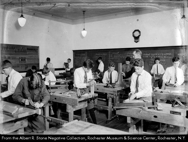 Carpentry students work on their projects at Martin B. Anderson School No. 1 on Hillside Avenue in Rochester NY.  1922. Old School No. 1, on Winton Road near East Avenue, was transferred from Brighton to Rochester ca.1904-1905 and used by the City School District as Martin B. Anderson School No. 1 for many years.