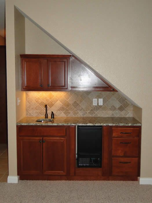 A bar under the stairs in the basement - a great use of space - under stairs kitchen storage