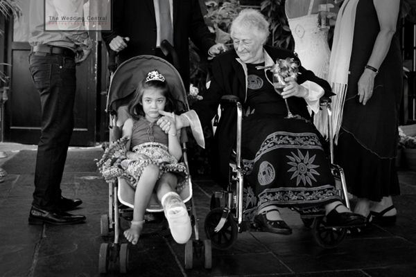 Two generations - Flower girl and grandmother sit side by side as everyone gathers around them for family portraits during a wedding