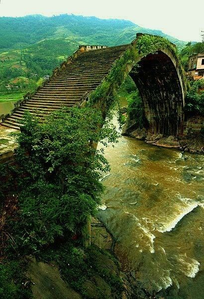 Ming Dynasty Bridges, China. surreal but real. Yulong Bridge was built in Yongle Period Ming Dynasty. It is a stone bridge with a length of 36 meters, a width of 4.2 meters and a height of 9 meters. Expressing a magnificent feeling, Yulong Bridge is in a simple style but featured minority characters. Yulong Bridge is located in the Yulong River Scenic Area. Without any man-made attractions, this area is the largest natural landscape garden.