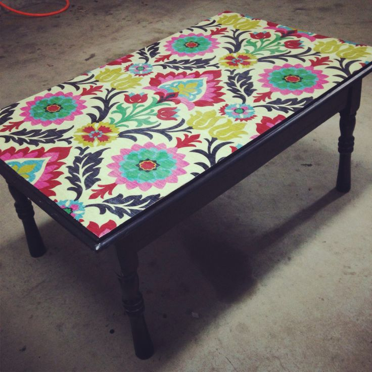 Mod Podge (decoupage) fabric onto a castaway coffee table. Preserve with a few coats of acrylic sealer