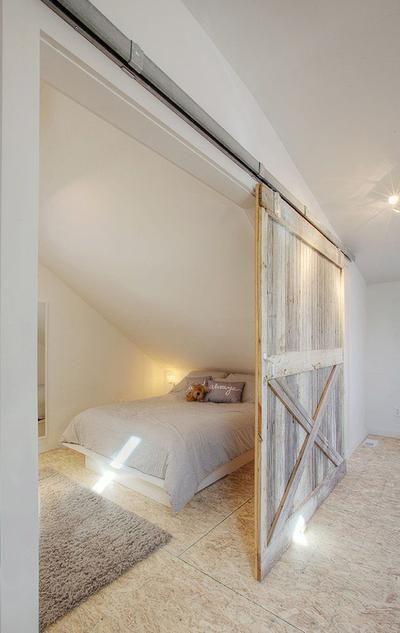 Mooie landelijke slaapkamer in een afgescheiden deel van de zolder. De grote landelijke schuifdeur maakt de sfeer helemaal af.