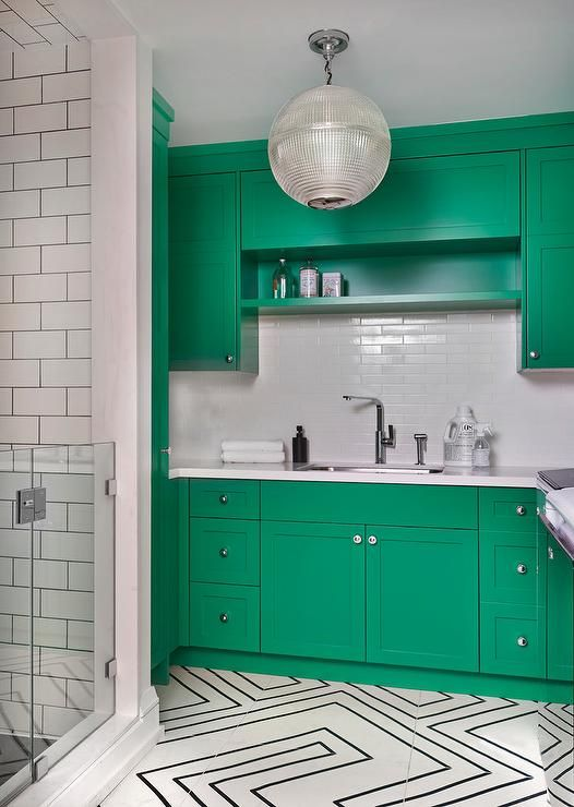 Kelly green shaker cabinets provide a pop of color to this beautiful contemporary laundry room and are finished with a white quartz countertop fitted with a curved stainless steel sink paired with a modern polished nickel faucet kit mounted in front of linear white backsplash tiles.