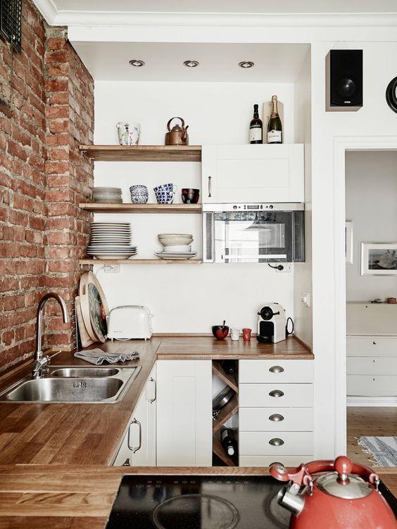 Białe szafki z drewnianym blatem i czerwone cegły w kuchni