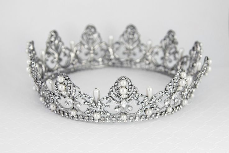 Not available until May! Make a glamorous statement with this royal, full circle bridal crown. Ivory teardrop pearls alternate with regal rhinestone covered designs set in antique silver or gold. Sure