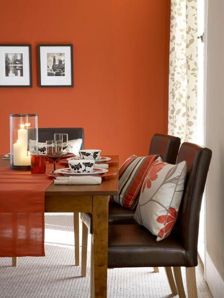 Deep orange walls lend a formal feel to this party-ready dining room. For a…