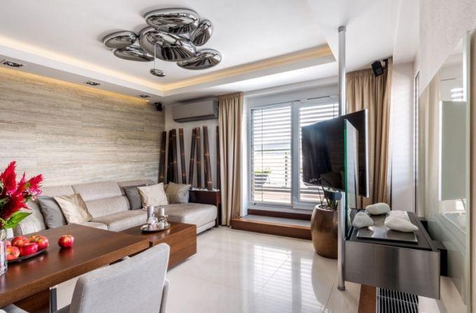 Obývací pokoj není moc velký. Zdobí ho přisazené stropní svítidlo Skydro (Artemide). Aby bylo možné umístit pohovku (Natuzzi) s výhledem ven, je televizor připevněn na tyči