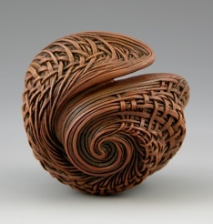 """""""Sea of Entwined Dreams"""", carved/ textured cherry, acrylics. Jacques Vesery is an Artist/ Sculptor from Damariscotta and has lived in Maine for 20 years. Striving to create an illusion of reality, his vision and inspiration begins with repetitive patterns derived from the 'golden mean' or 'divine proportions'. The marriage of pattern, form and proportion conveys a sense of growth from within each of his pieces."""