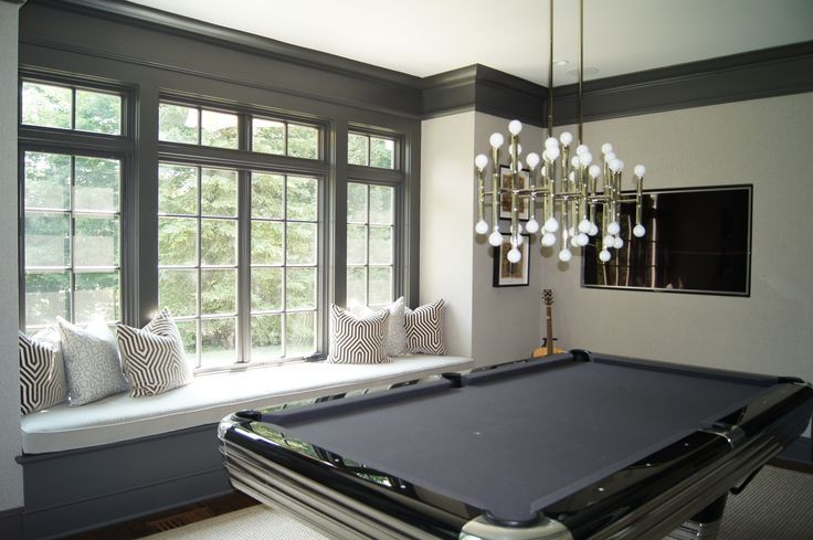 Chic gray game room features light gray walls accented with charcoal gray crown moldings and base boards framing built-in window seat accented with white and gray geometric pillows, Mary McDonald Vanderbilt Velvet Dove Fabric Pillows under windows trimmed in gray moldings.