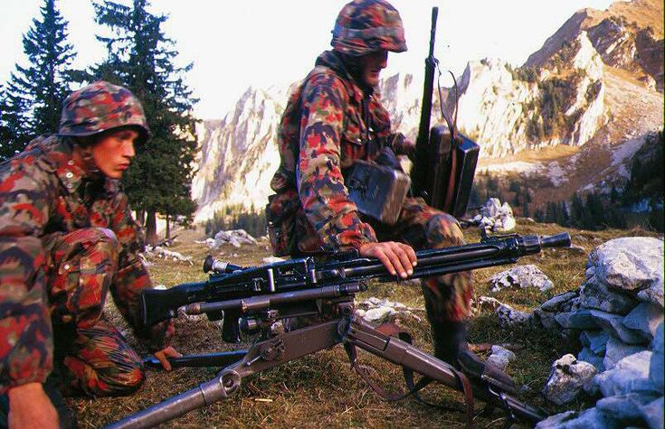 Swiss Infantrymen set up the Swiss copy of the German MG42 Machine-Gun during a training exercise in either the 1970's or 1980's. The soldier on the right carries the standard Swiss Infantry rifle ; The Stg. 57.