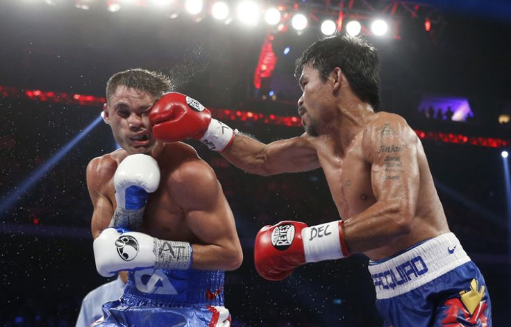 WBO welterweight champion Manny Pacquiao (right) from the Philippines lands a right on the face of WBO junior welterweight champion Chris Algieri of the United States during their welterweight boxing title fight in Macau
