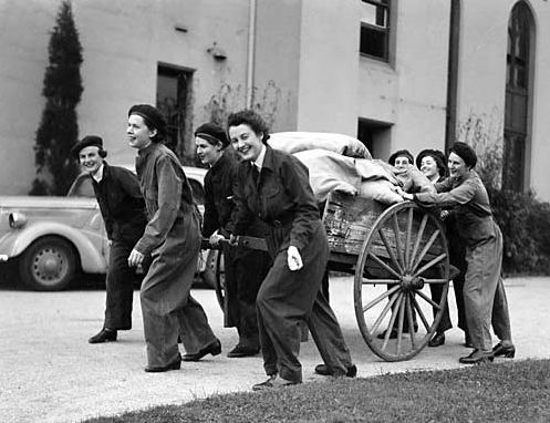 Women's Auxiliary Australian Air Force (WAAAF) recruits carrying their straw-filled palliasses back to their barrack huts at No 1 WAAAF Training Depot Detachment, No 1 School of Technical Training, RAAF, West Melbourne, Victoria. c 1941