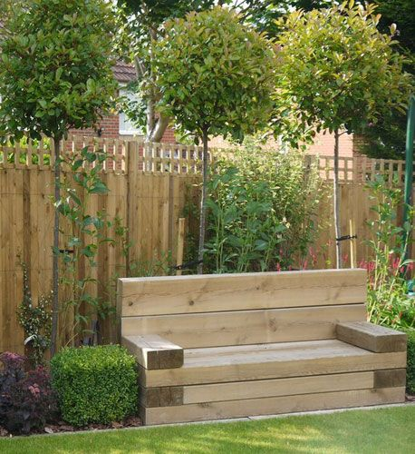 Standard Photinia fraseri Red Robin trees screen the neighbouring property, while clipped Buxus cubes frame the sleeper built seat. Hydrangea arborescens Annabelle is underplanted with Brunnera macrophylla Jack Frost with Clematis Perle DAzure trained on the fence behind.
