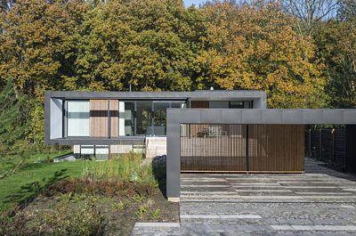 Dům i chráněné místo k stání pro auta mají sjednocený vzhled. Na obou se střídá falcovaný zinkový plech v tmavě šedé barvě a dřevěné latě.