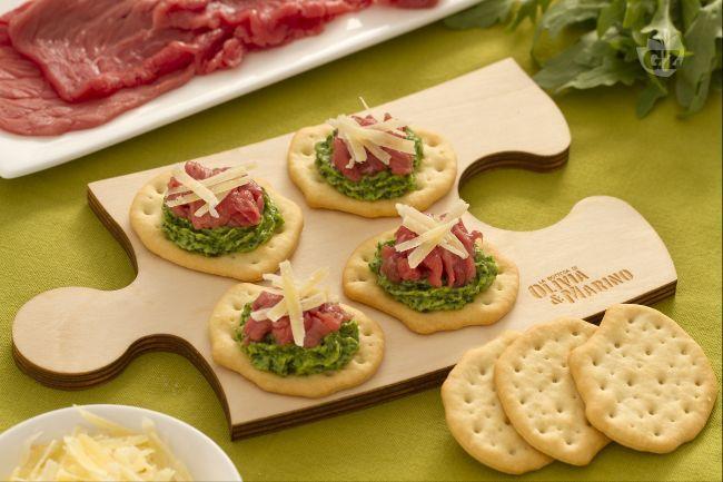 Le schiacciate con carpaccio di manzo, rucola e sbrinz sono un finger food delicato e gustoso con carpaccio di manzo, pesto di rucola e sbrinz.