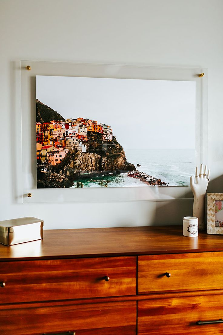 a boho-minimalist bedroom makeover, featuring the lucite and brass Float Frame from Artifact Uprising! Plus, enter the giveaway to win a frame for your own home! All of the details are on Jojotastic.com @artifactuprsng and travel photography by @heydanfredo of Cinque Terre