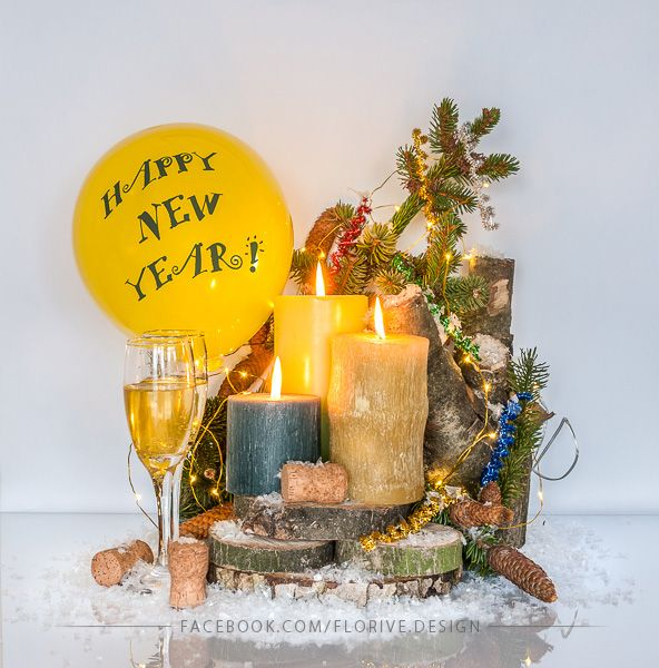 New Year's decoration with the inscription of New Year, burning candles and glasses of sparkling champagne on the wood pieces